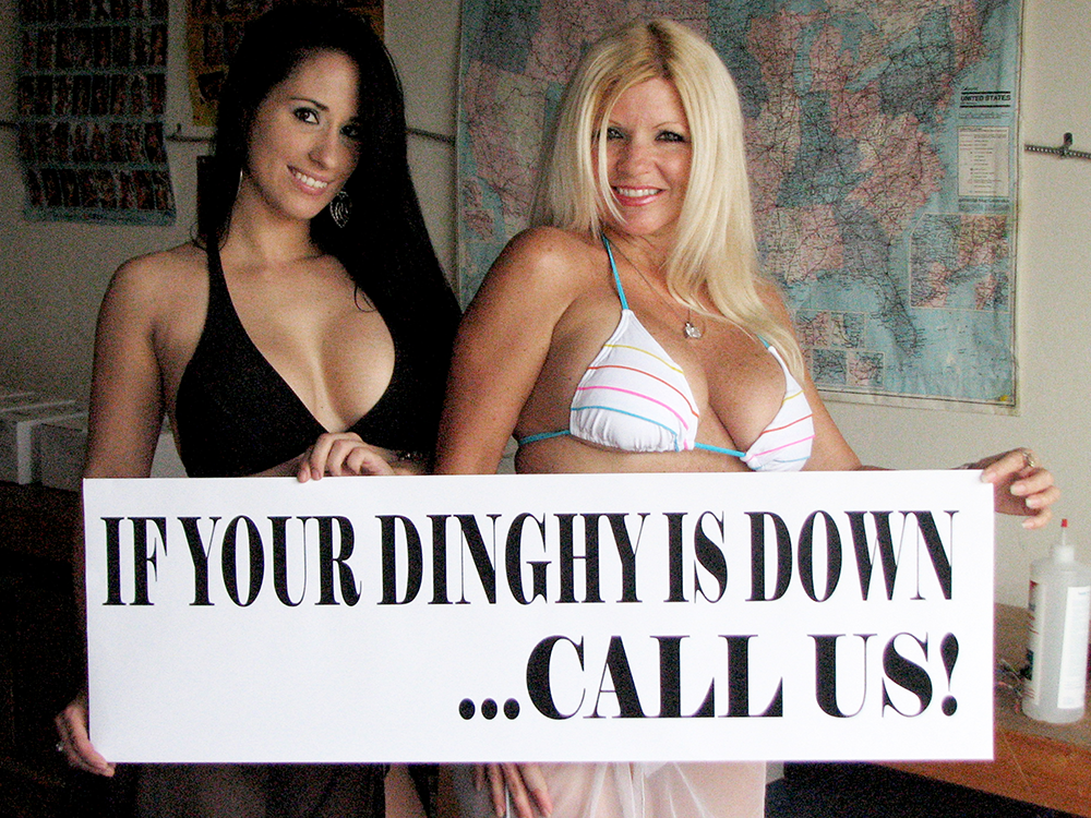 "women holding sign that says ""If your dinghy is down... call us!"""