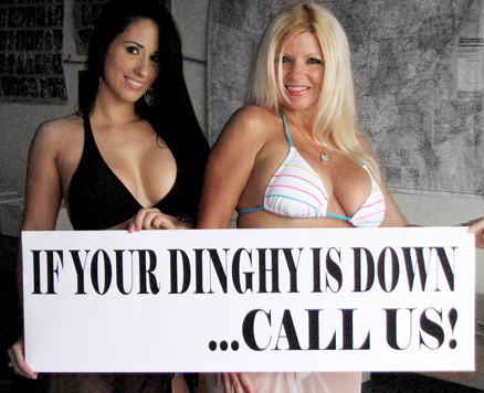 "woman holding sign that says ""If your dinghy is down... call us!"""